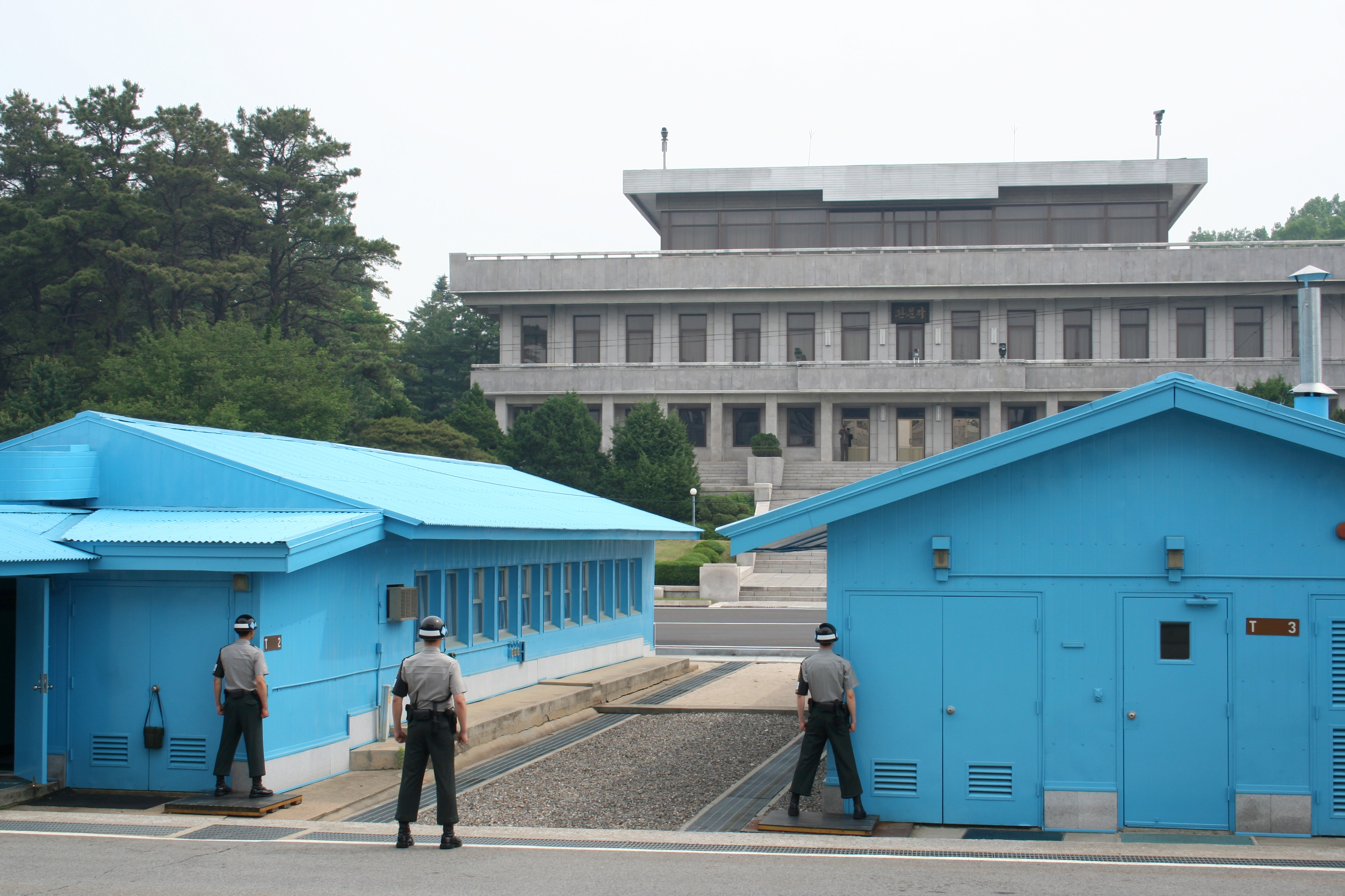 Conference Row at the Joint Security Area in Korea, seen from the South Side. The building in the background is Panmun House. The concrete line running through the huts is the MDL, the official border between the two countries. The ROK solders stand with half of their body obscured in order to provide a smaller target to those on the North, as well as to be able to signal unseen if necessary.